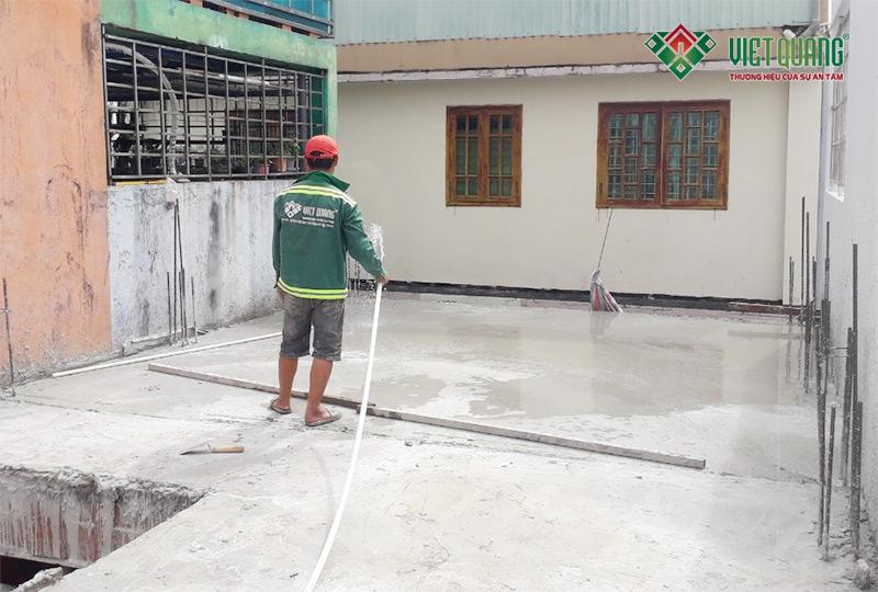 Công nhân Việt Quang tưới nước cho bê tông nhằm cung cấp độ ẩm cho bê tông