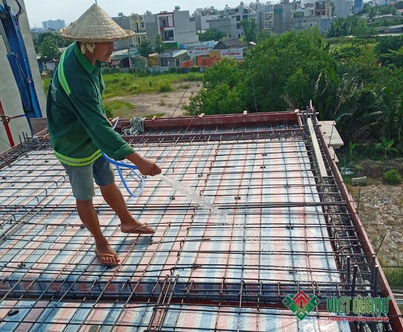 Công nhân tưới nước vệ sinh sàn sạch sẽ và tạo đổ ẩm trước khi đổ bê tông sàn