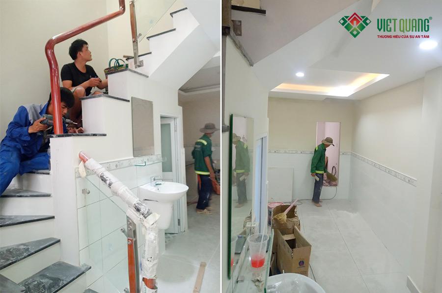 Công nhân đang gắn kính cường lực cầu thang (bên trái) và công nhân đang dọn đẹp vê sinh công trình (bên phải)